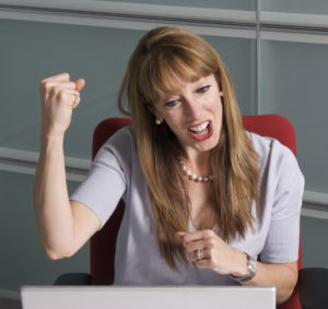 Woman seated at computer raising her hand in triumph