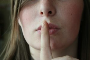 Young girl with finger pressed to lips like a secret