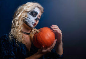 woman holding pumpkin with ghoulish mask
