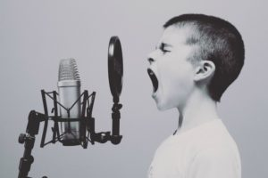 young boy shouting into a microphone